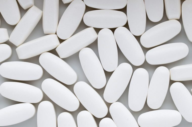 White pills on the white background.