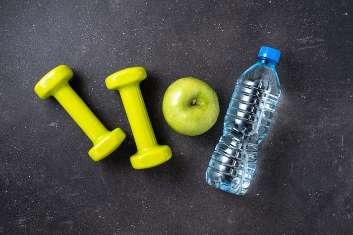 Fitness concept with dumbbells, water and green apple on dark background