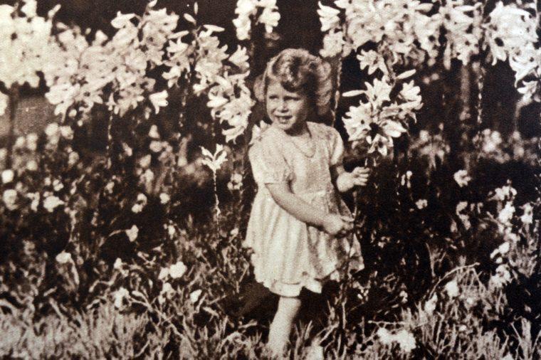 VARIOUS Princess Elizabeth later Queen Elizabeth II, as a child, gathering flowers in a garden, 1930.