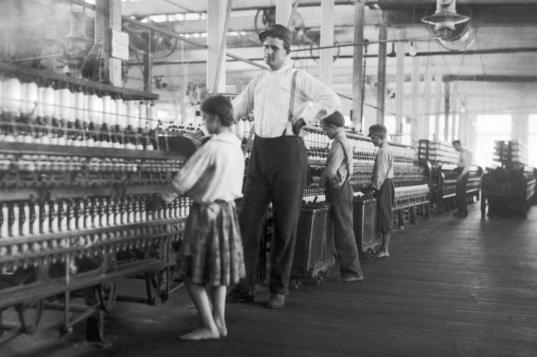 A young spinner being watched by the overseer at Yazoo City Yarn Mills.