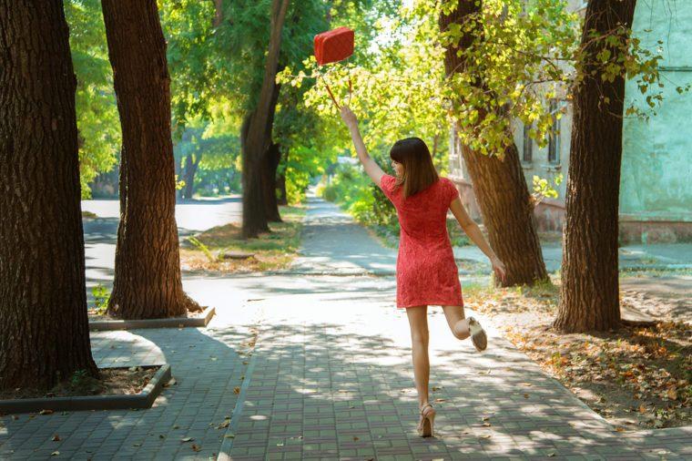 Young beautiful girl having fun skipping walking down the street, waving her handbag