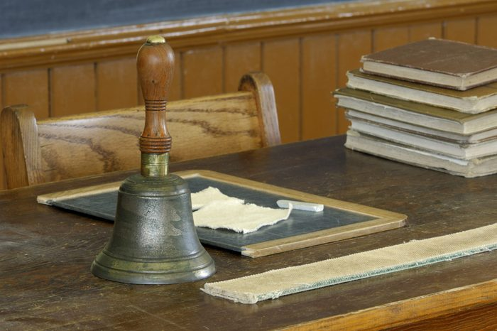 school teacher's desk with books, slate, chalk, bell and strap