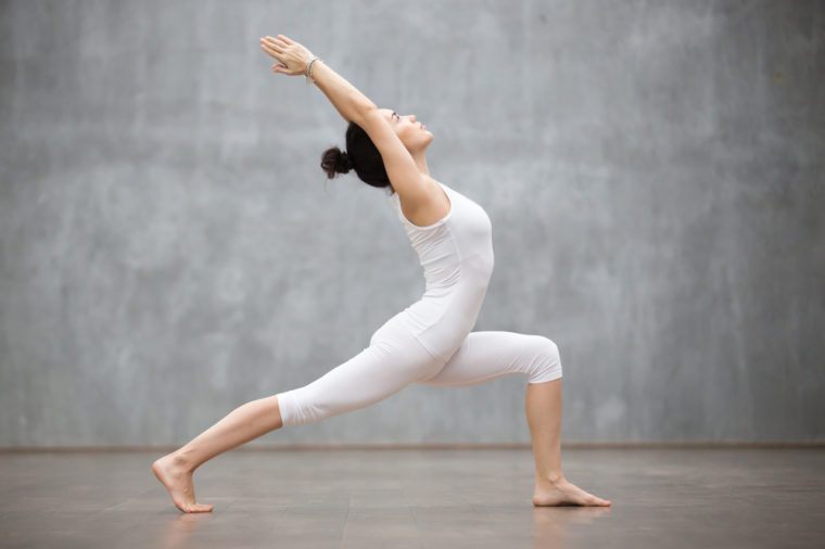 Side view portrait of beautiful young woman wearing white tank top working out against grey wall, doing yoga or pilates exercise. Standing in Warrior one pose, Virabhadrasana. Full length