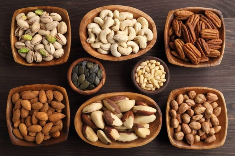Different kinds of nuts in wooden bowls.