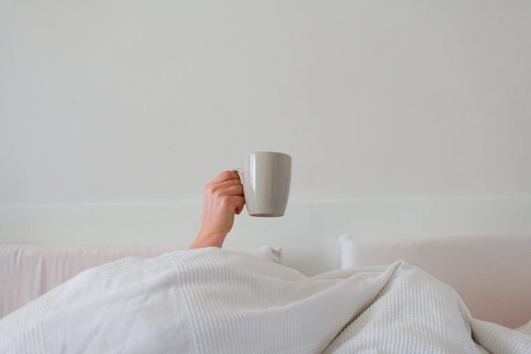 hand in bed with coffee