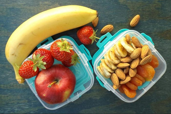 Apple, strawberry and banana in a transparent container. Two different lunch boxes. Dried fruits and nuts in a plastic container