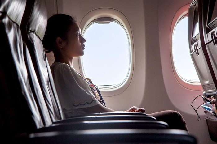 Woman sitting in a flying aircraft and watching the monitor. Passengers relax on the plane.