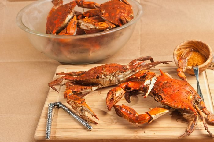 Two steamed, seasoned, male jumbo Chesapeake Bay blue claw crabs on a wood cutting board with nut cracker and a wood bowl of seasoning and a clear glass bowl of crabs on brown paper table cloth