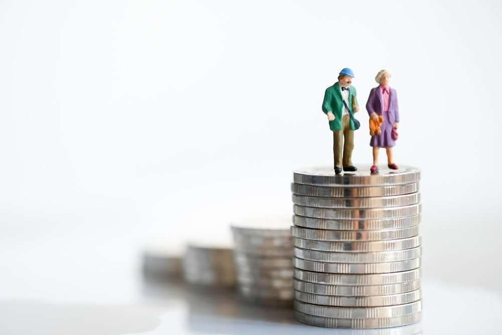 Miniature people: Old couple figure standing on top of stack coins using as background retirement planning concept.