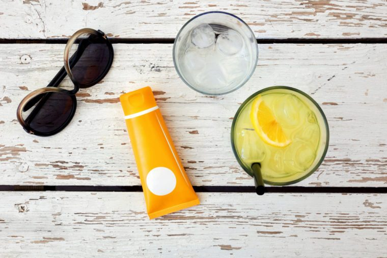 Top view of sunglasses, sunblock, glass of lemonade and water on a white wooden table. Concept of beach accessories and holiday