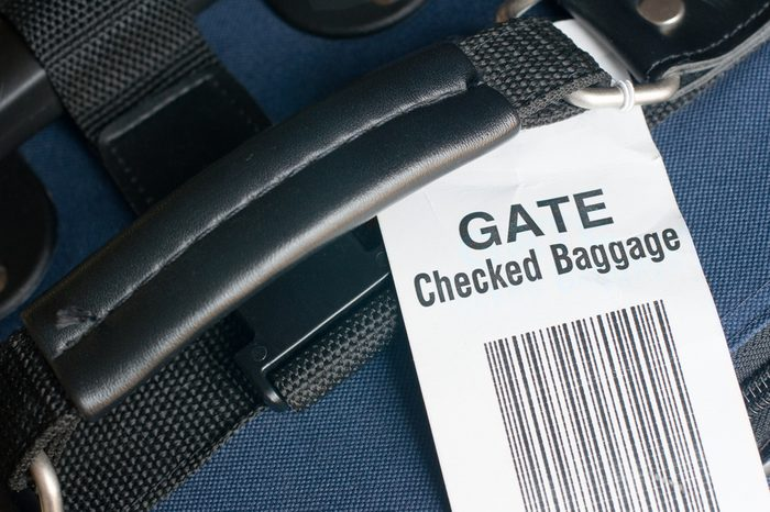 Close up of airline checked baggage label on blue suitcase. Attached at the departure gate to carry on luggage that is too big for aircraft cabin. Horizontal view.