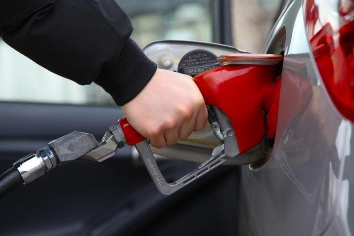 Gas pump refilling automobile fuel. Shallow focus.