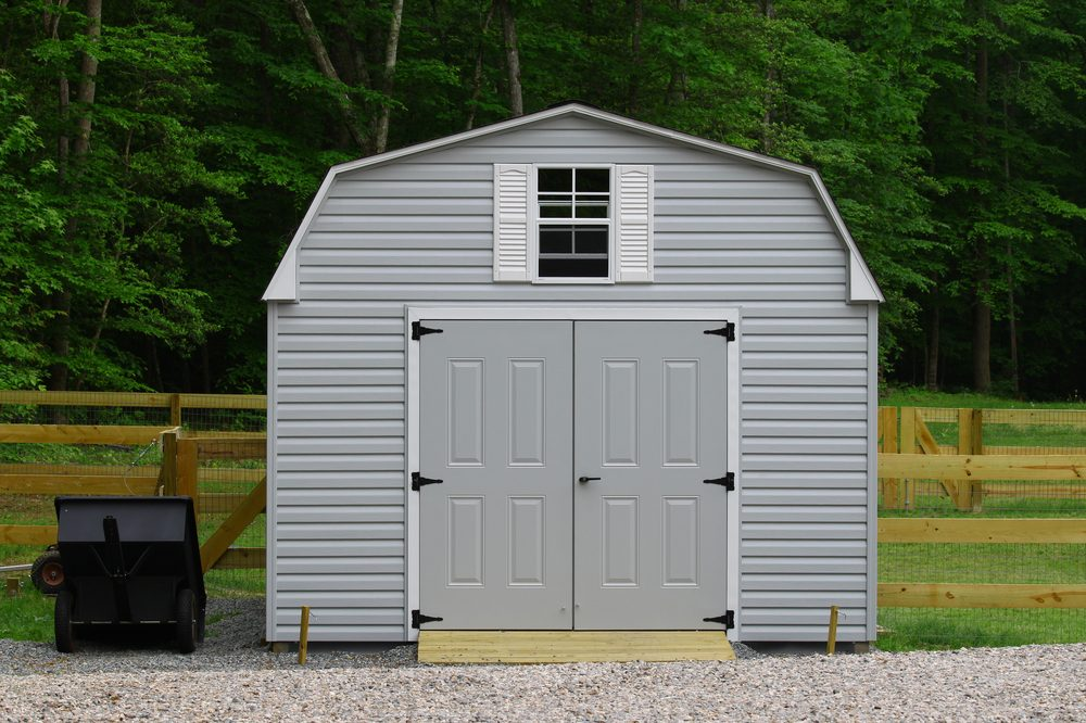 A nice new storage shed outside of a fenced in back yard with a trailer beside it with room for your text.