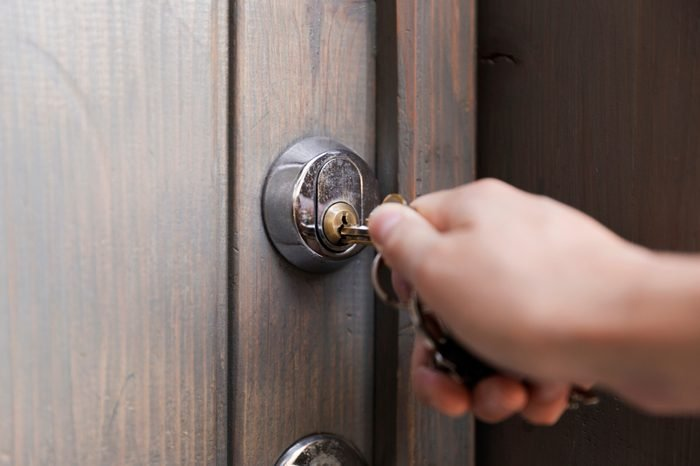 Woman's hand puts the key in the keyhole of wooden door. Home security concept