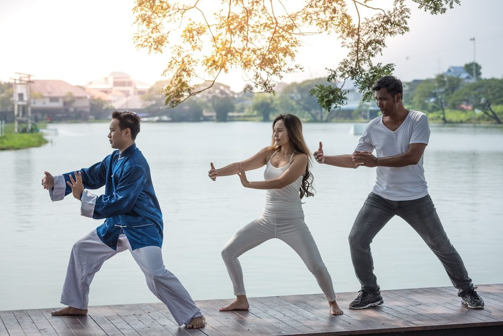 Group of young people practicing traditional Tai Chi Chuan, Tai Ji  and Qi Gong for fighting match together in the park on the lake background, traditional chinese martial arts concept.