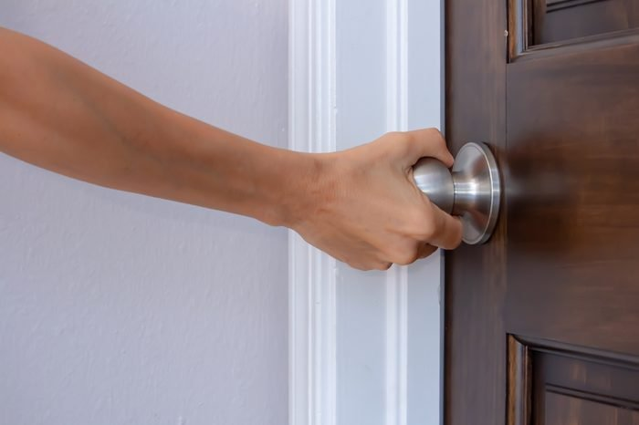a woman's right hand turning a doorknob to close or open it palm turned away from camera, privacy trust safety security concept, horizontal shot, white copy text space, closeup side view