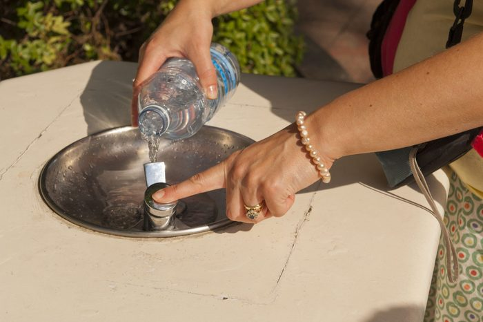 VARIOUS Model Released - People filling bottles with water from the drinking fountains at Disneyland Paris in France
