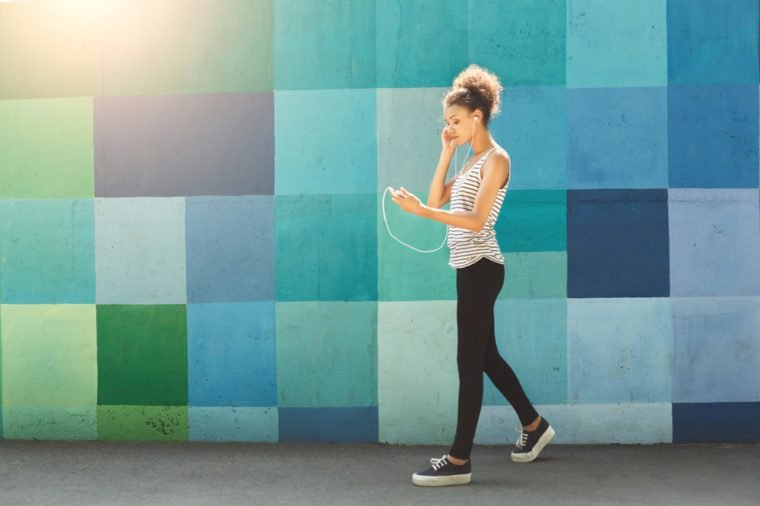 Thoughtful african-american woman posing at bright blue graffiti wall, while listening music, relaxing from jog training, copy space, side view