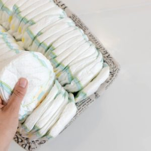 Stack of baby disposable diapers and Pacifier over white background; Shutterstock ID 650657350