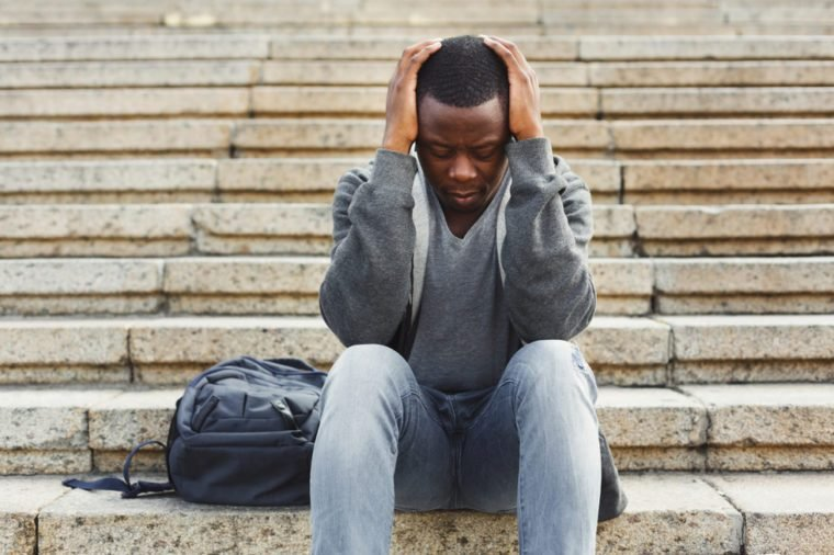 Desperate african-american student sitting on stairs outdoors in university campus. Man raised hands to his head. Migraine, education and overworking concept, copy space