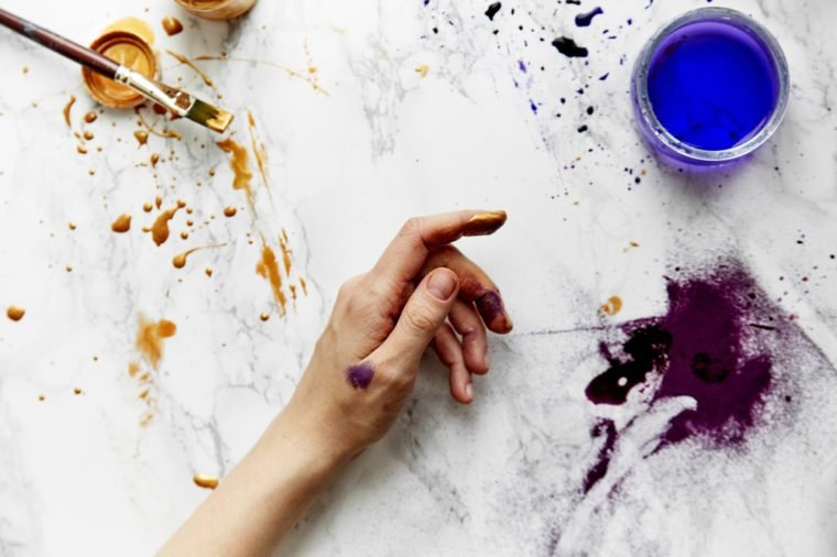Overhead view of female artist hands soiled with golden and violet paints on white background. Artist workspace concept.