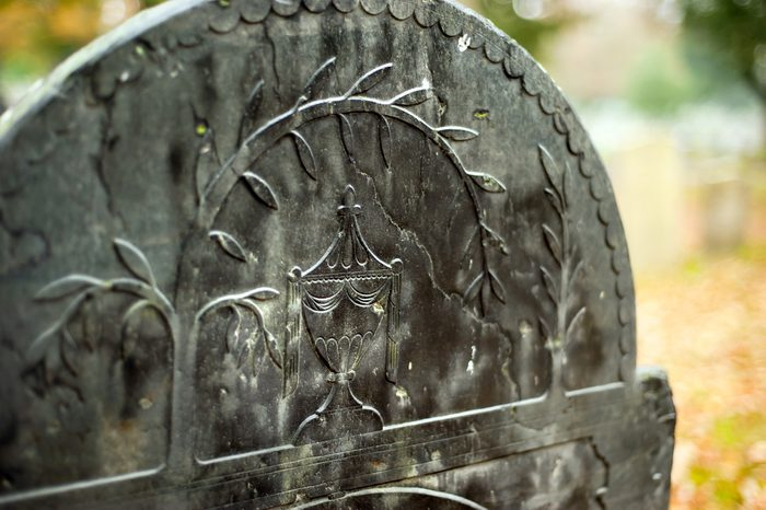 Detail of a gravestone in a cemetery during autumn.
