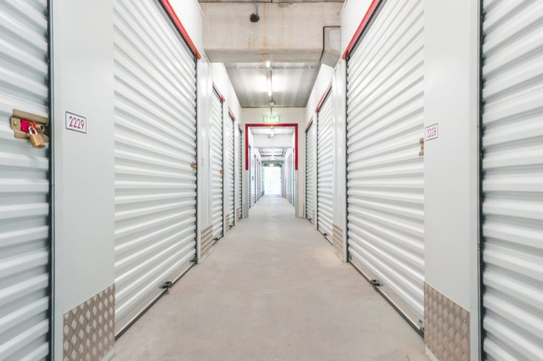 Hallway with white storage units. Concrete floor