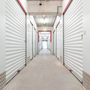 Hallway with white storage units. Concrete floor