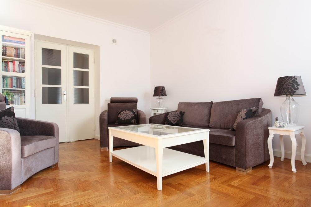 Spacious living room with wooden floor and bright walls