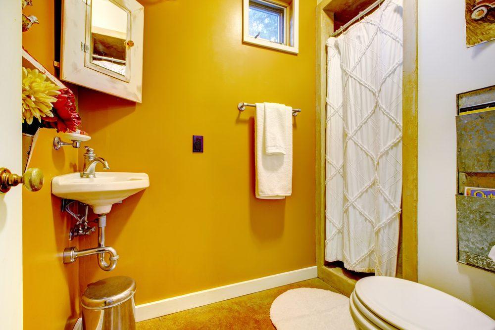 Bright mustard yellow interior of unique vintage style bathroom