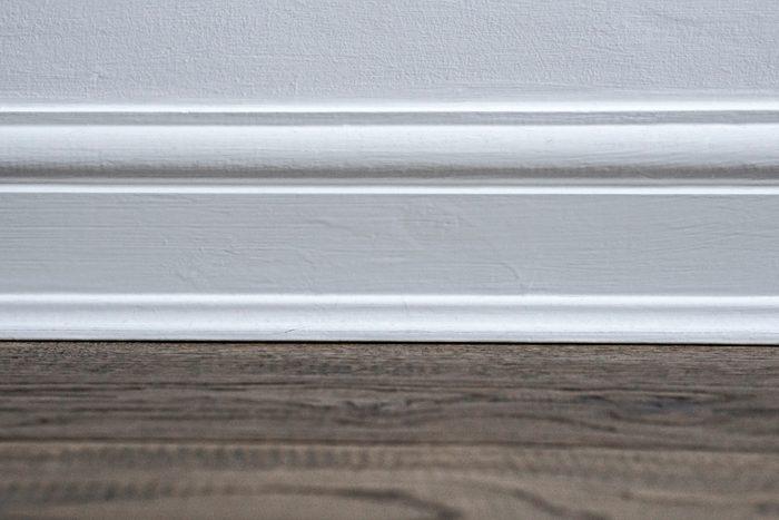 Plain white wooden skirting board against a dark wooden floor.