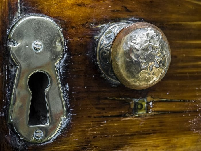 An old, weathered brass door knob and key hole with layers of old polish.