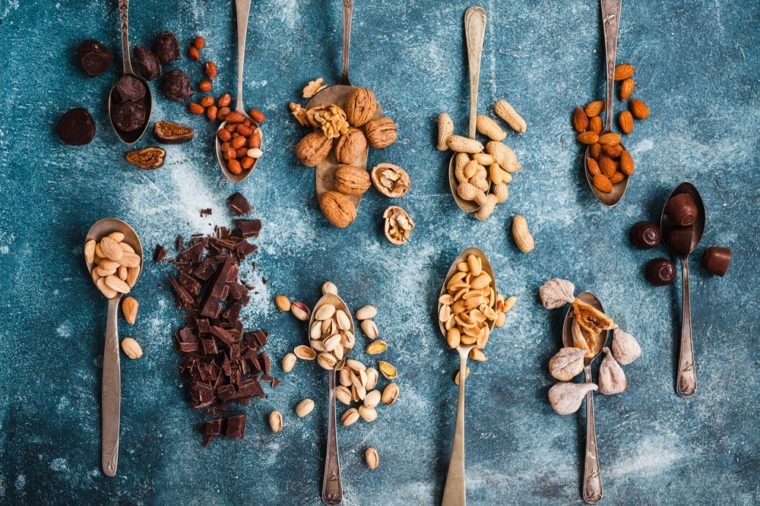 Food in spoons. Variety nuts, chocolate cut, figs in spoons. Overhead of mix chocolate, bonbon, nuts, figs over blue table ready to prepare granola.