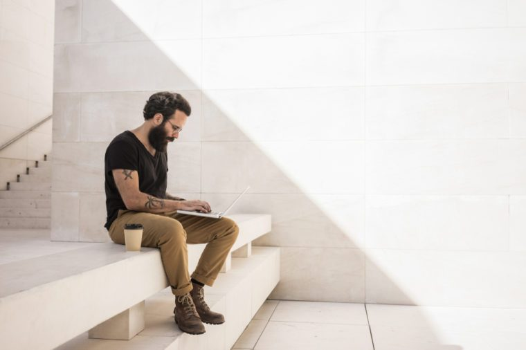 Bearded man sits on shade of minimalistic and geometric space with his computer working on project. Man is very concentrated and wears generic stylish outfit with leather boots.