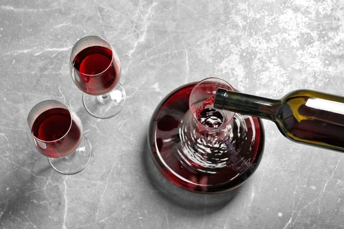 Pouring delicious red wine into decanter on grey table, above view