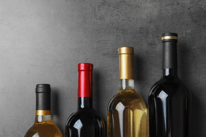 Bottles with delicious wine on grey background, top view