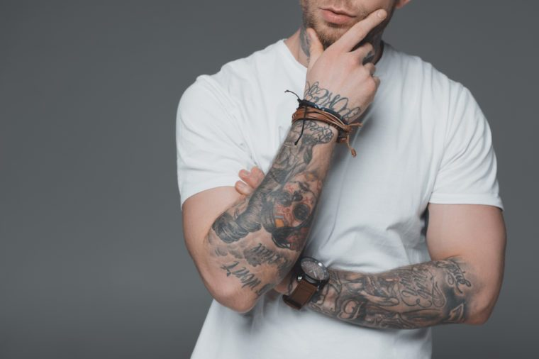 cropped shot of stylish young tattooed man in white t-shirt standing with hand on chin isolated on grey