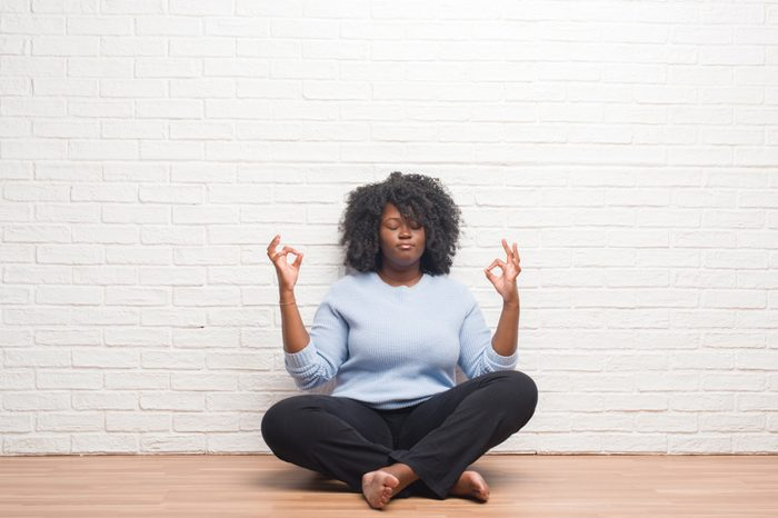 Young african american woman sitting on the floor at home relax and smiling with eyes closed doing meditation gesture with fingers. Yoga concept.