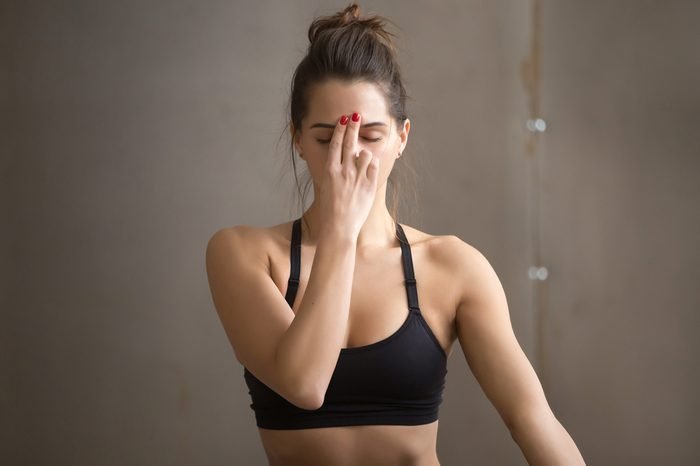 Portrait of young attractive yogi woman practicing yoga, making Alternate Nostril Breathing, nadi shodhana pranayama exercise, working out, cool urban style, closeup, grey studio background