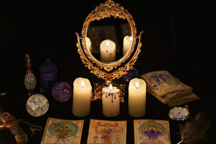 Fortune telling ritual with the Tarot cards, mirror, crystals and vintage objects. Halloween concept, black magic still life or witch spell with occult and esoteric symbols, divination rite.