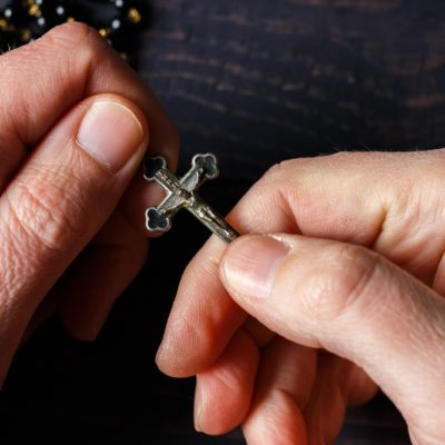 The hand holds a rosary close-up on a dark wooden background