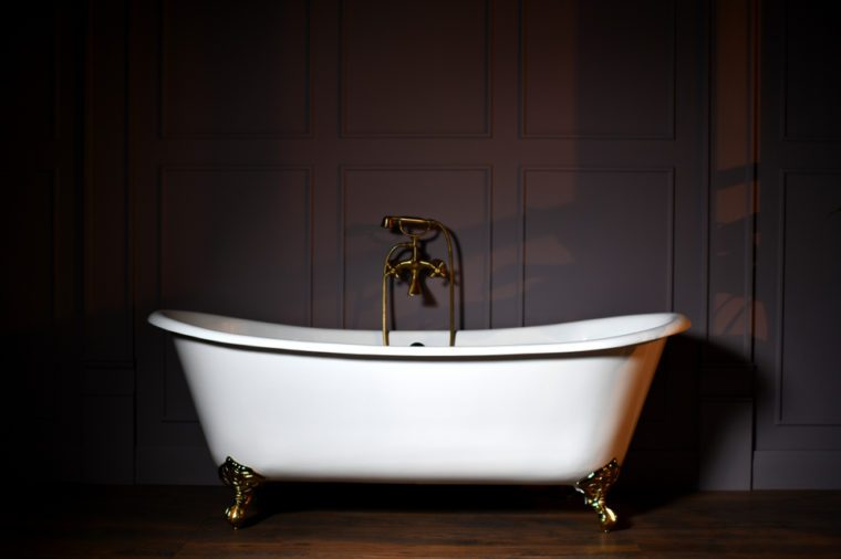 Beautiful classic style white claw foot bathtub with stainless steel old fashioned faucet and sprayer on dark background