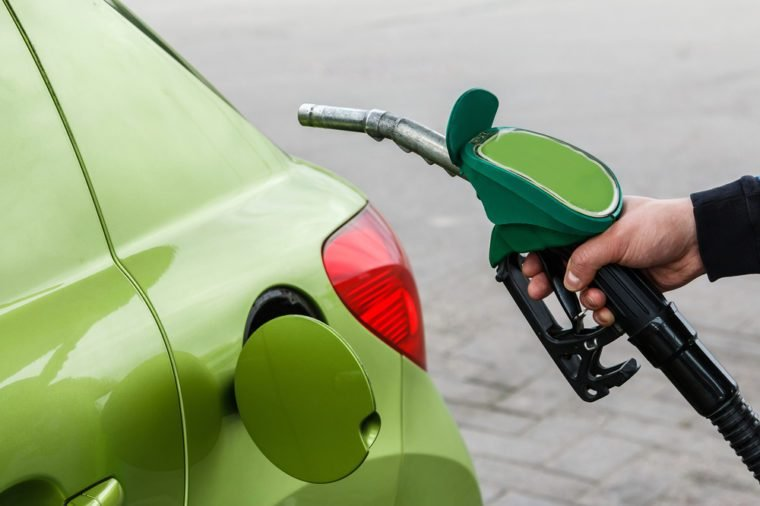 Man fills up his car with a gasoline at gas station