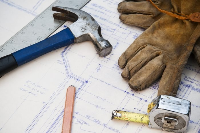 blue prints at a work site with tools and gloves
