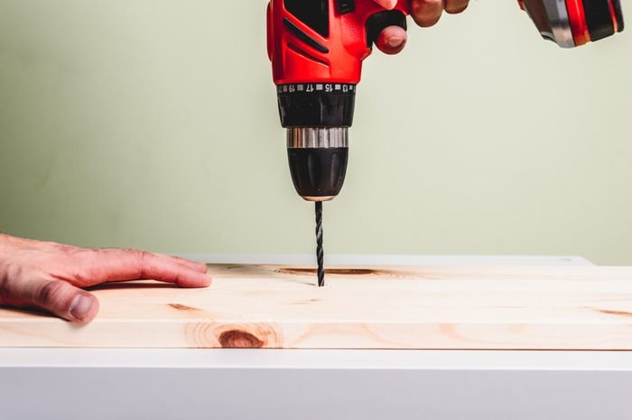 A red screwdriver drills a hole in a wooden board. Making wooden products, the concept of manual labor.