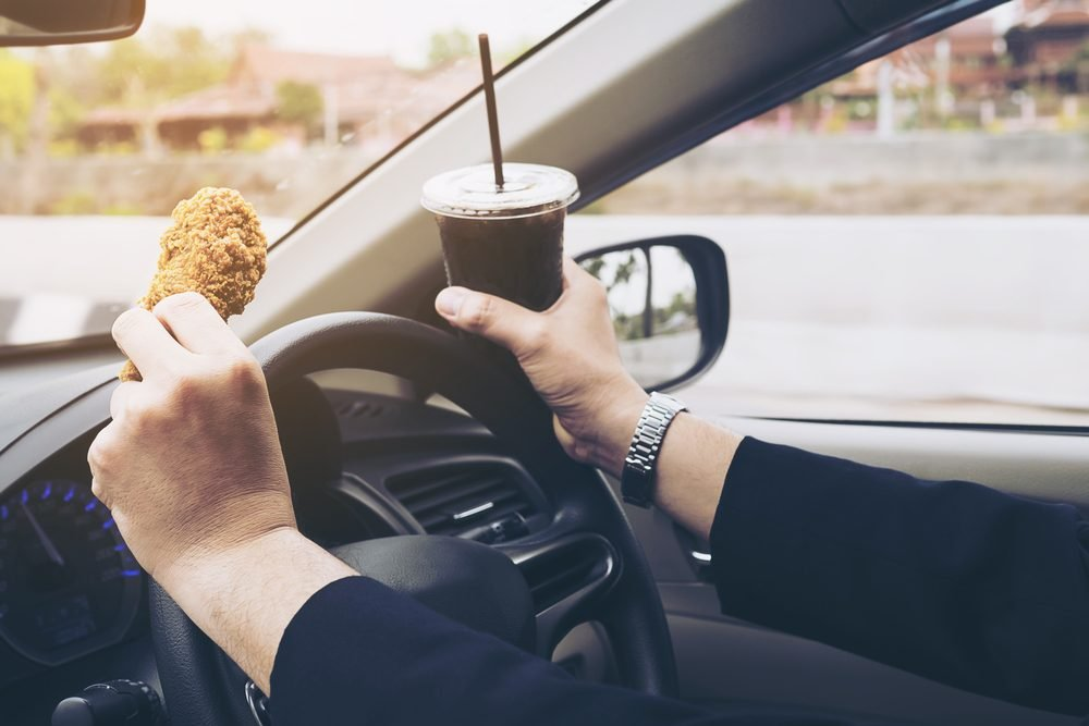 Business man driving car while eating fried chicken and cold soft drink dangerously