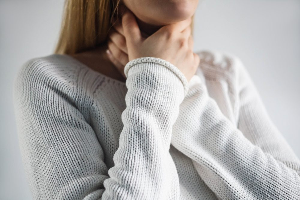 Sore throat of woman.Touching the neck