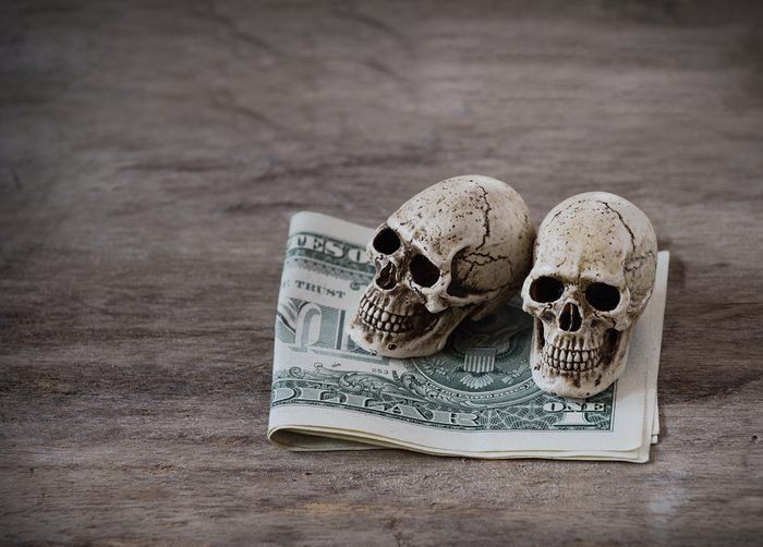 Still life skull and US dollar banknote on grunge wood board,hard work less income concept.