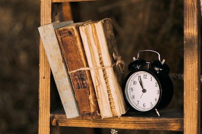 Old books on the shelf clock