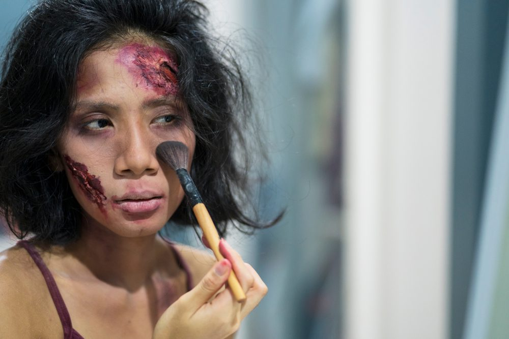 Young woman putting some special effects makeup on face